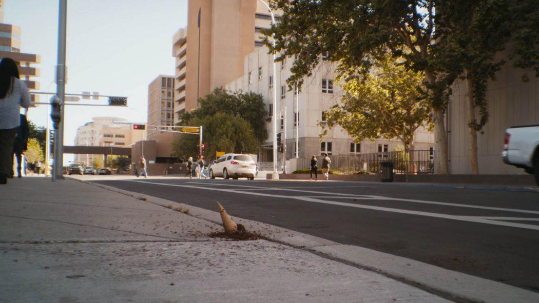 Um sorvete de casquinha caído numa calçada cheio de formigas mais de longe