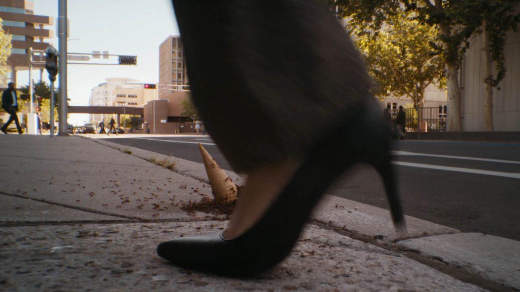 Um sapato passando na frente do sorvete cheio de formigas