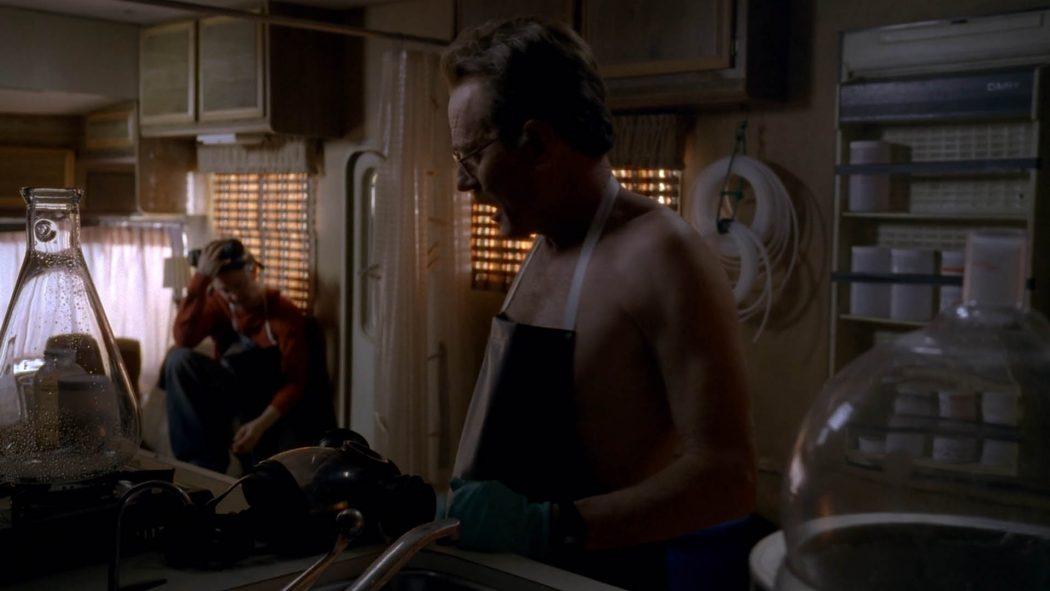 Walter de avental conversando com Jesse Pinkman em meio aos materiais químicos