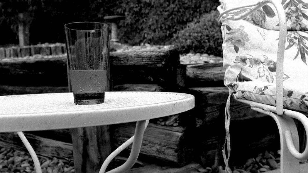 um copo com uma bebida gelada em uma mesa no jardim