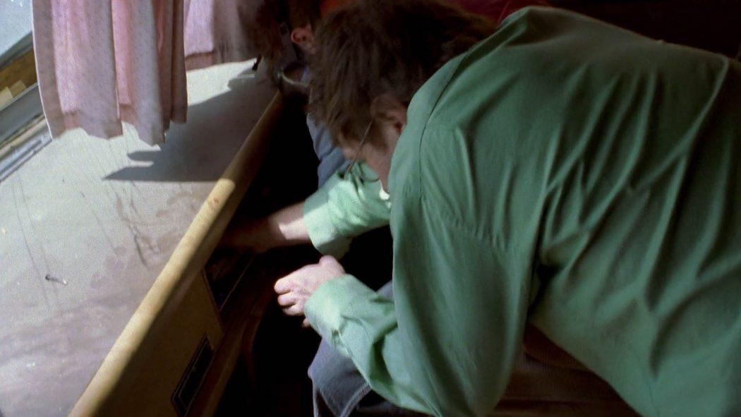 Walter pegando uma câmera no porta-luva do trailer