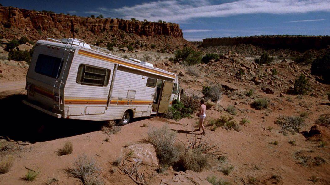 Trailer atolado no deserto com um homem de cueca do lado de fora