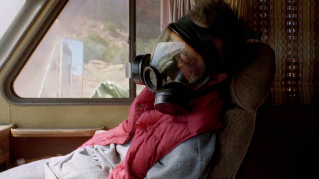 Jesse Pinkman apagado de máscara química sentado no banco do carona