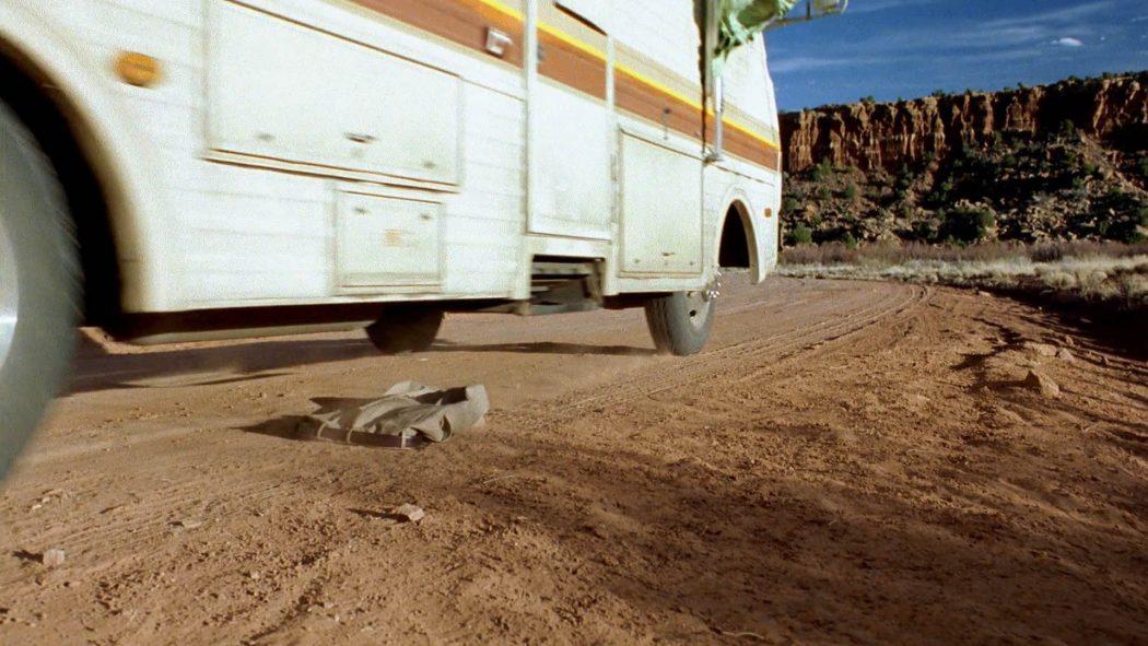 Um trailer passando em cima de uma calça em uma estrada de terra no deserto