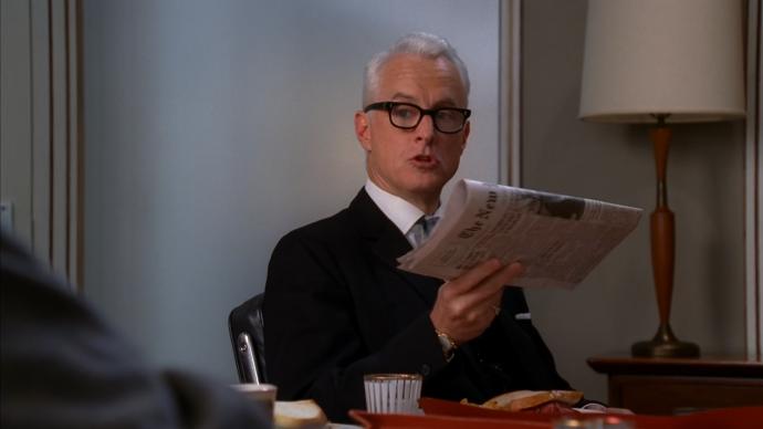 Roger segurando um jornal dobrado