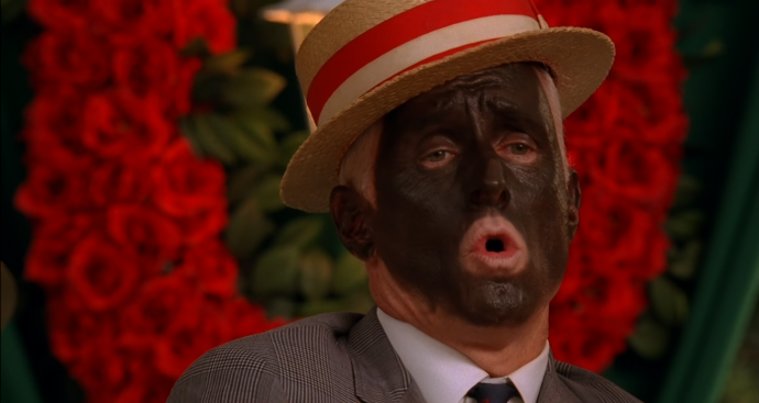 Roger cantando com o rosto pintado de preto.