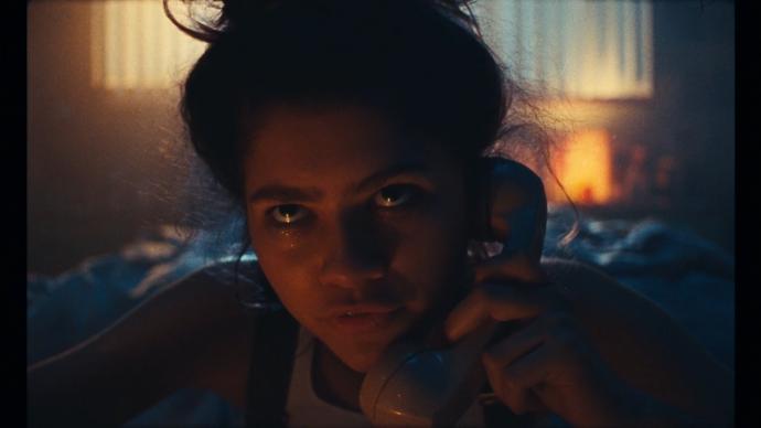 Rue vestida de detetive segurando um telefone no seu quarto escuro