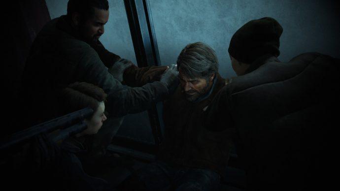 The Last of Us Parte II: Joel sendo segurado contra a parede por dois homens da WLF enquanto Mel faz um torniquete em sua perna e Owen aponta uma escopeta para o seu rosto