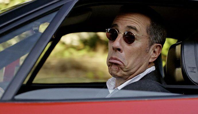 Jerry Seinfield olhando pela janela do carro para a câmera com um ar irônico de surpresa