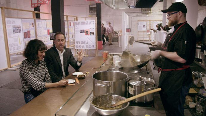 Jerry Seinfield e Melissa Villaseñor sentados em uma bancada comendo em frente a um fogão com um cozinheiro mexendo uma massa na panela, tudo ao lado de uma exposição
