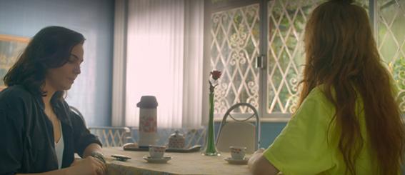 Verônica conversando com Janete que usa uma camisola. Ambas estão sentadas na mesa da sala de Janete.