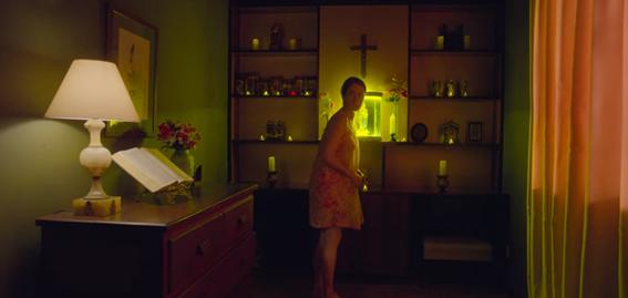 Janete, a noite, perto da estante da sala onde se encontra uma cruz.