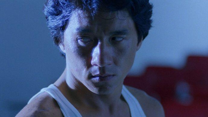 Jackie Chan olha sério para alguém fora de quadro