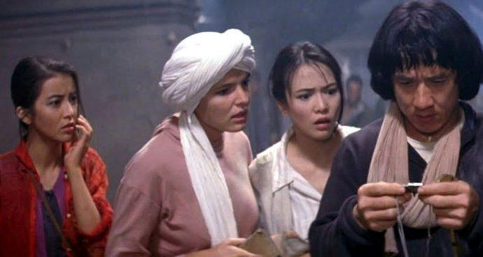 Carol Cheng, Eva Cobo, Shôko Ikeda eJackie Chan olham admirados para um objeto.