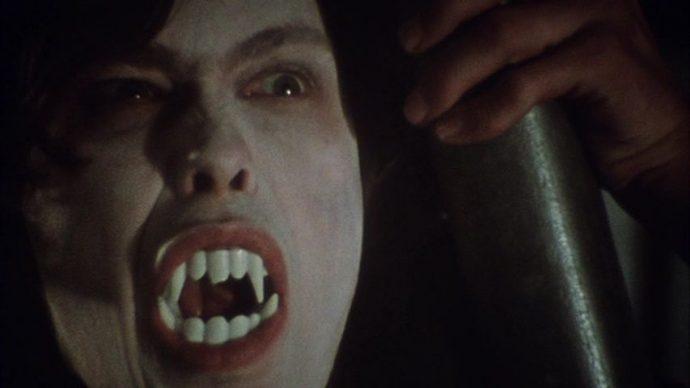 O rosto de Martin maquiado de branco, ele usa uma dentadura de vampiro