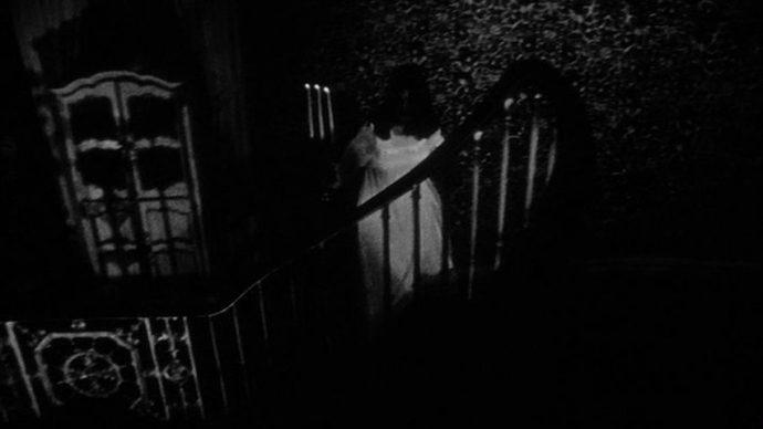 Uma mulher com um candelabro sobe uma escada