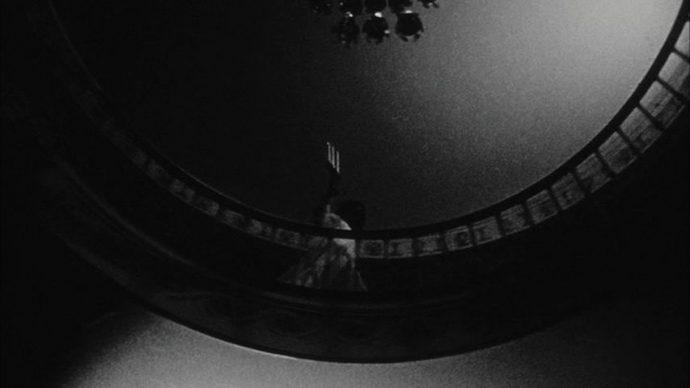 Uma mulher vista de baixo caminha com um candelabro