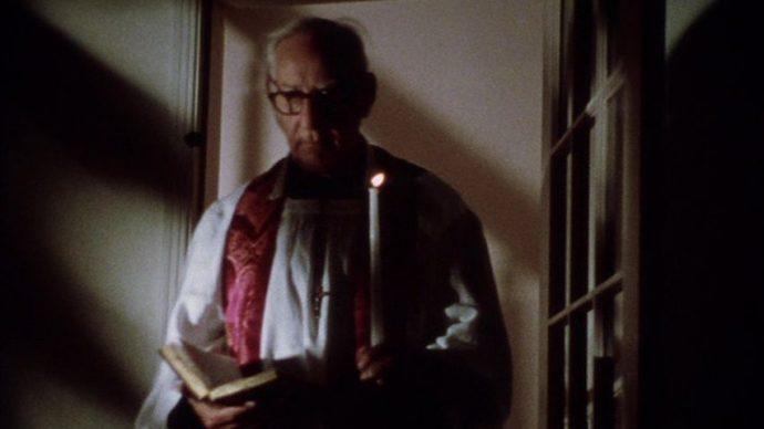 Padre idoso, tem a bíblia em uma mão e uma vela na outra