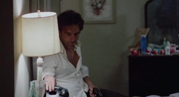 Nick completamente acabado, com o cigarro na boca e uma arma na mão, pega o telefone.