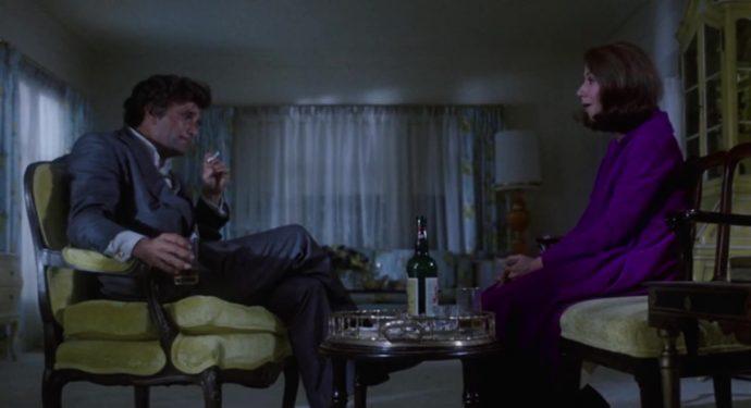 Mikey e sua esposa estão sentados frente a frete, eles estão uma sala de estra de uma casa classe média