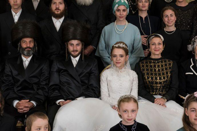 Uma criança ortodoxa vestida de noiva posa para uma foto em meio a diversos convidados