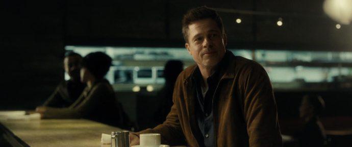 Brad Pitt sorri para alguém fora de quadro