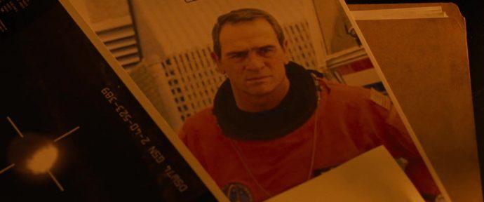 Uma foto do personagem de Tommy Lee Jones em meio a outras fotos e documentos