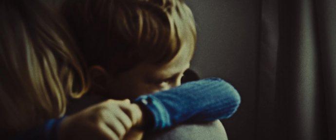 Uma criança abraçada a uma mulher olha pela janela, , a imagem parece fazer parte de um vídeo caseiro