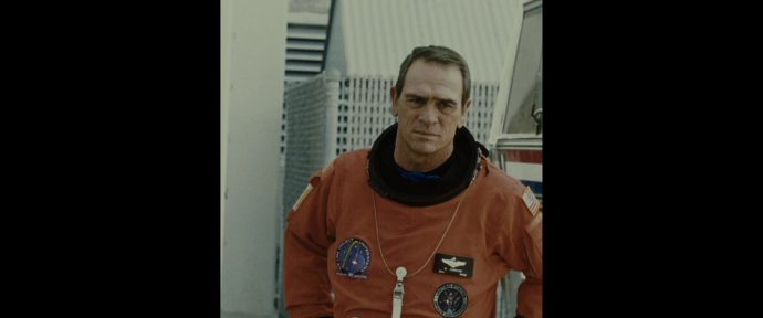 Foto do personagem de Tommy Lee Jones vestido como astronauta