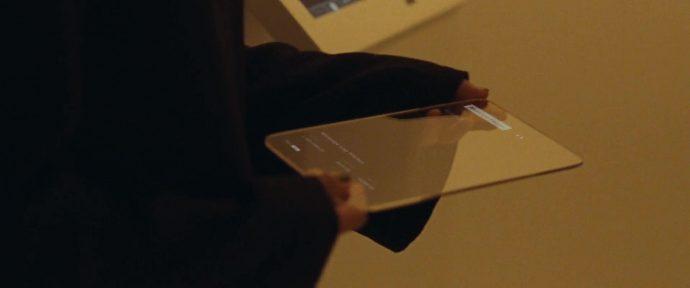 Plano detalhe de Helen pegando um tablet futurístico