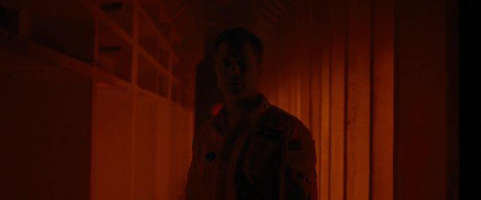 Plano fechado em Roy, o corredor fica cada vez mais escuro.
