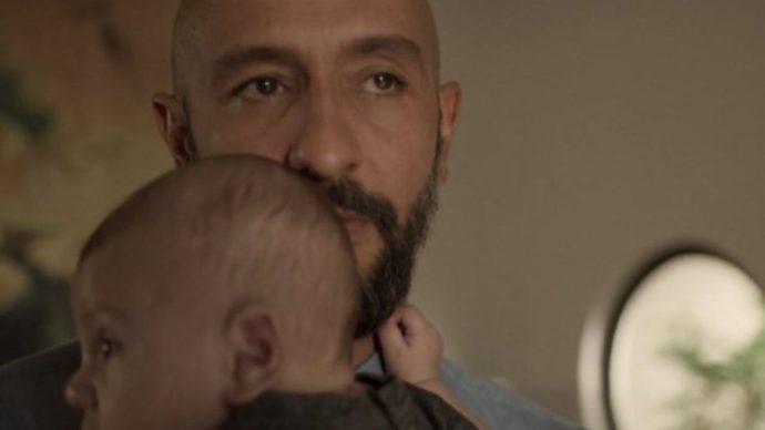 o personagem de Irandhir Santos, com um olhar ameaçador, segura um bebê