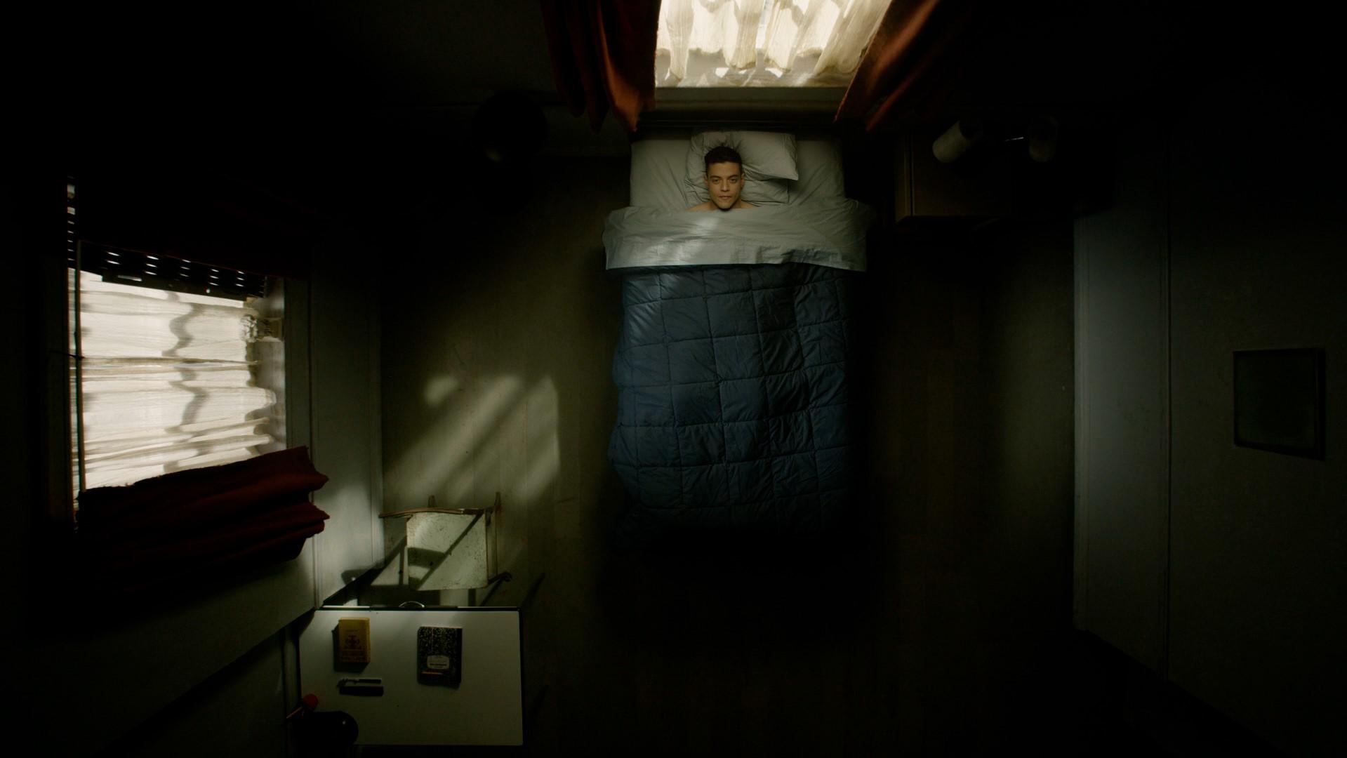 Elliot deitado na cama olhando para o teto do seu quarto de manhã