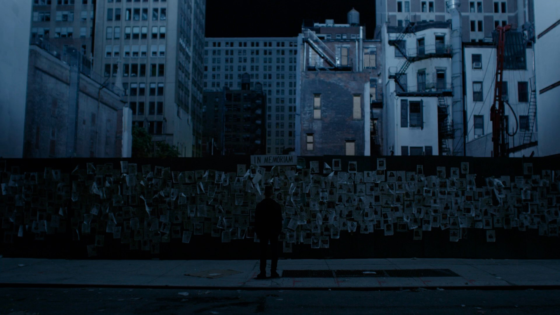 Elliot encarando uma parede com retratos em homenagem, enquanto as ruas estão apagadas sem luz