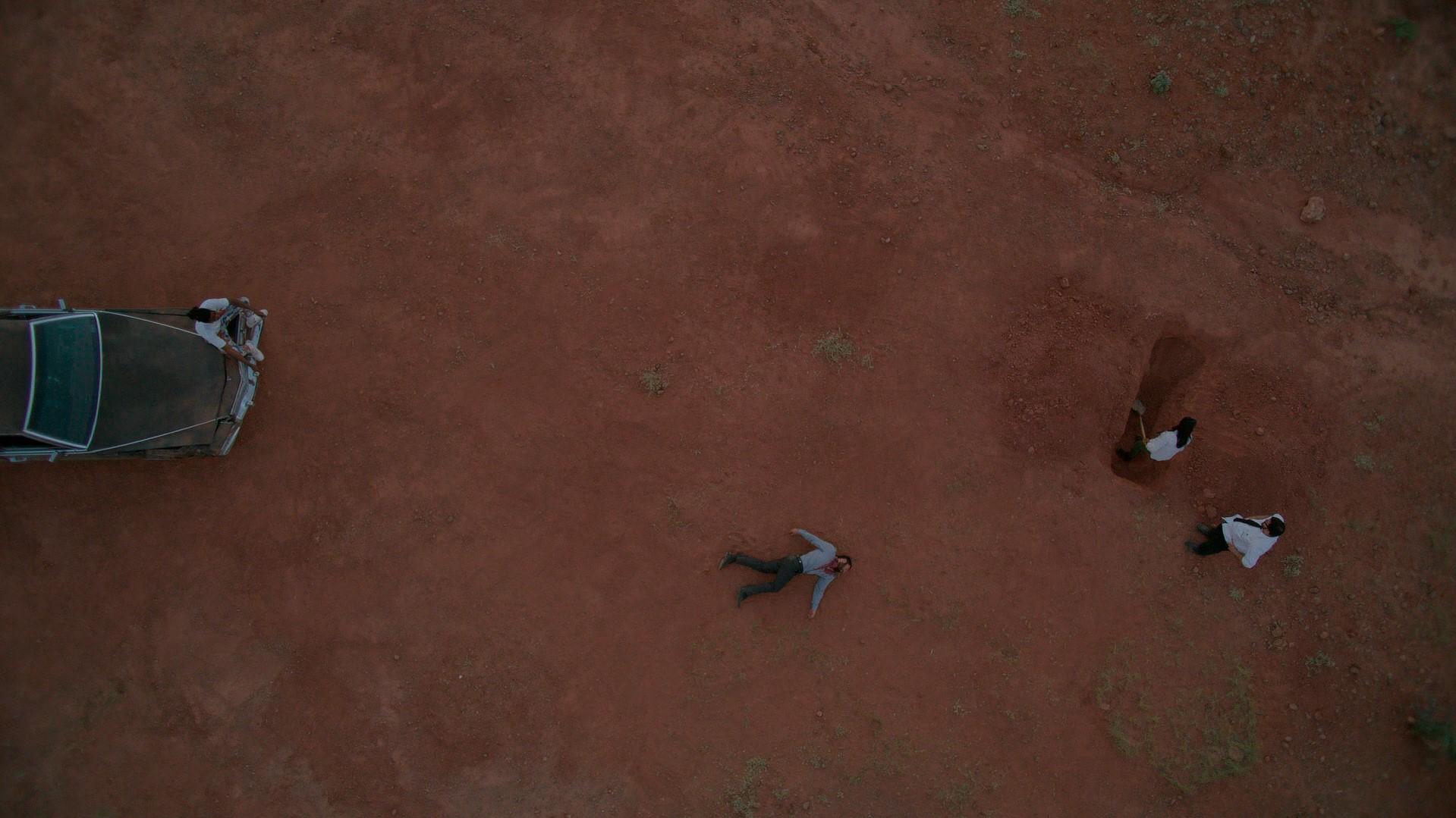 Mobley e Trenton cavando um buraco para esconder um corpo que está jogado perto. Enquanto Leon os observa sentado no capô de um cadillac amassado no meio do deserto