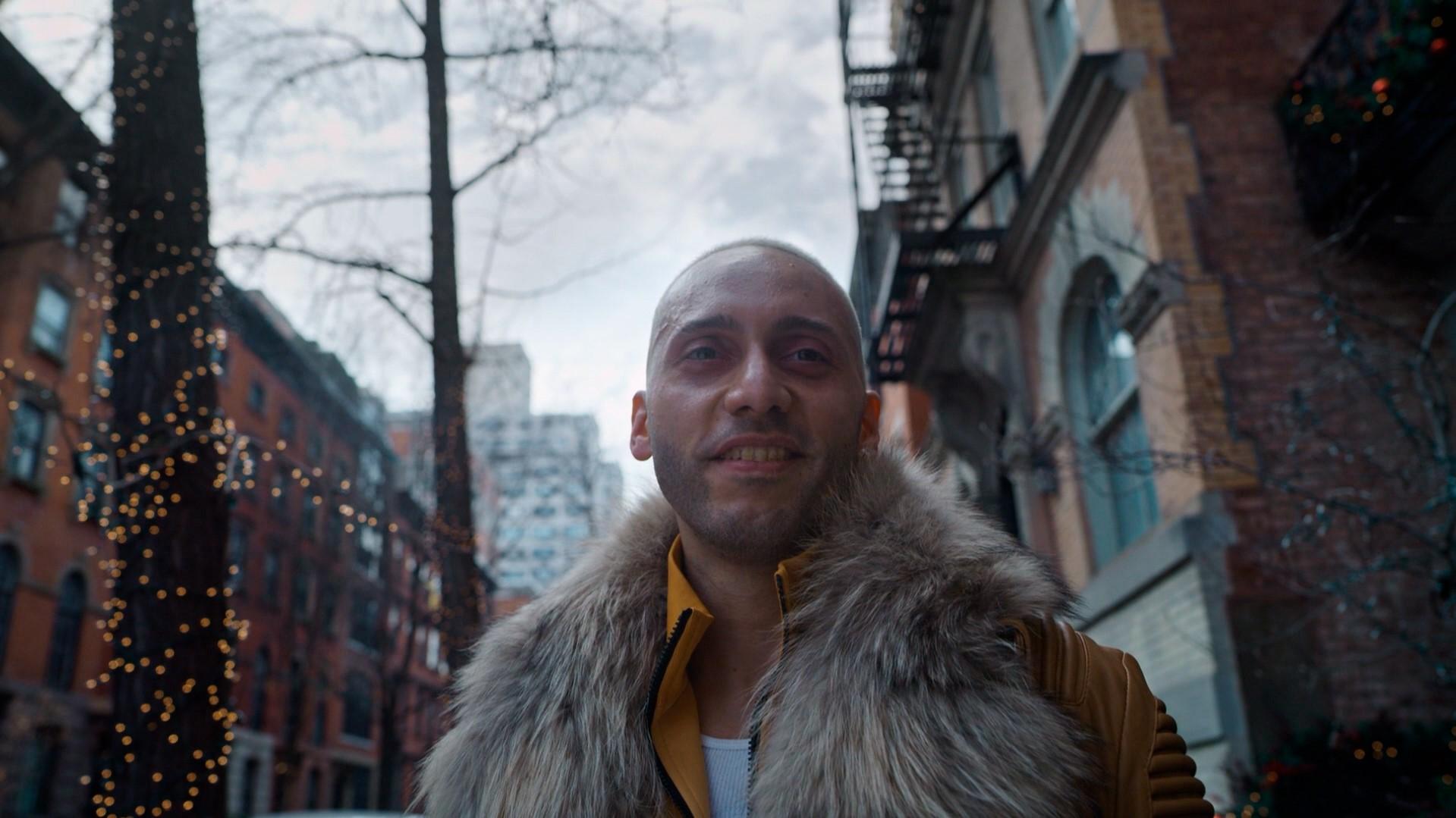 Fernando Vera de casaco amarelo encarando a câmera