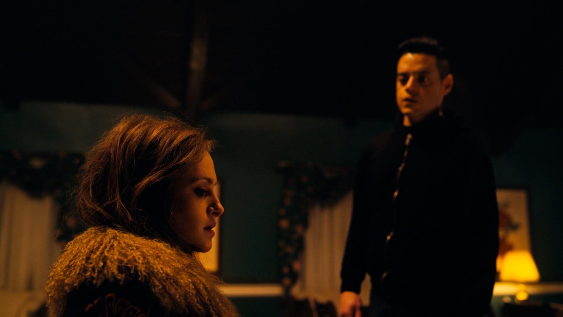 Elliot em pé ao lado de Darlene que está sentada