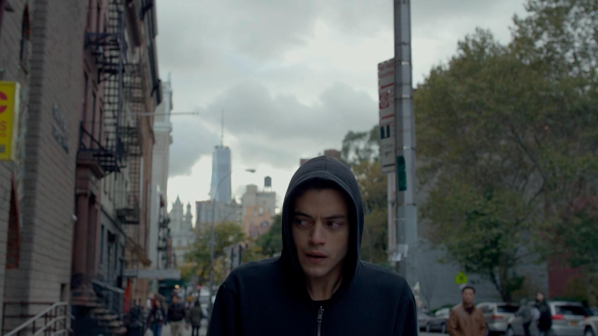 Elliot caminhando pela rua com um olhar suspeito de canto de olho