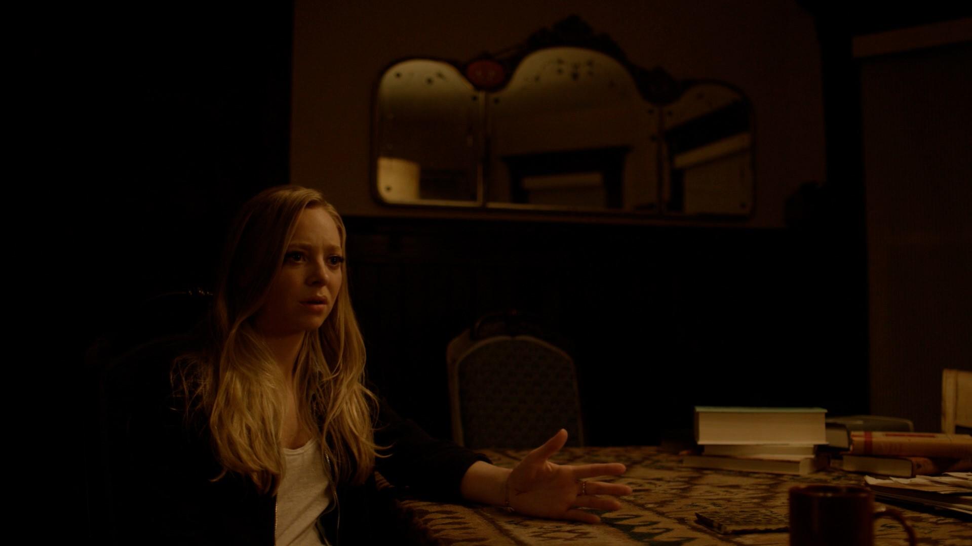 Angela sentada em uma mesa com uma pose argumentativa