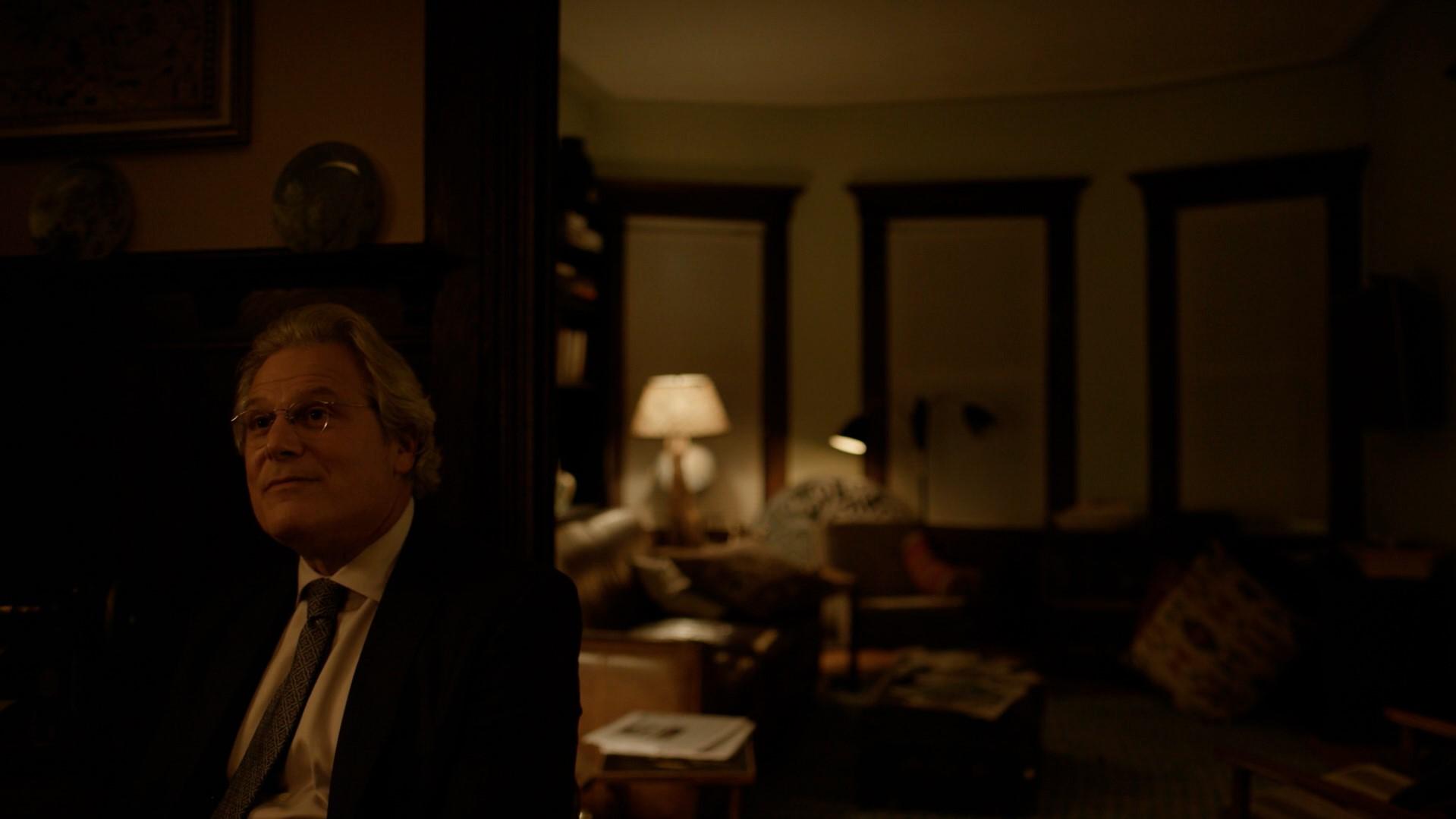 Terry Colby sentado na mesma mesa que Angela com uma aparência feliz