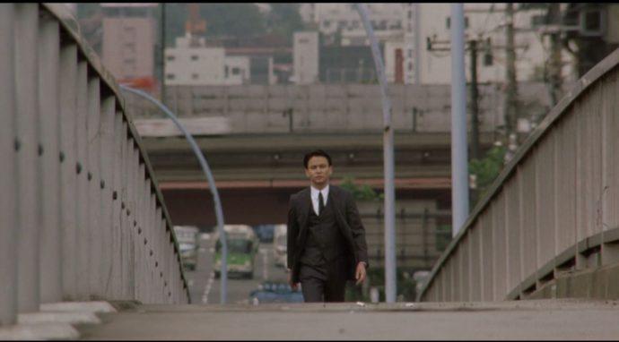 o personagem de Makoto Ashikawa caminha por uma ponte em direção a câmera