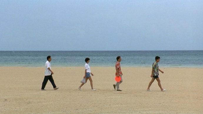 Cena do filme Sonatine. Quatro pessoas, três homens e uma mulher caminham em uma praia.