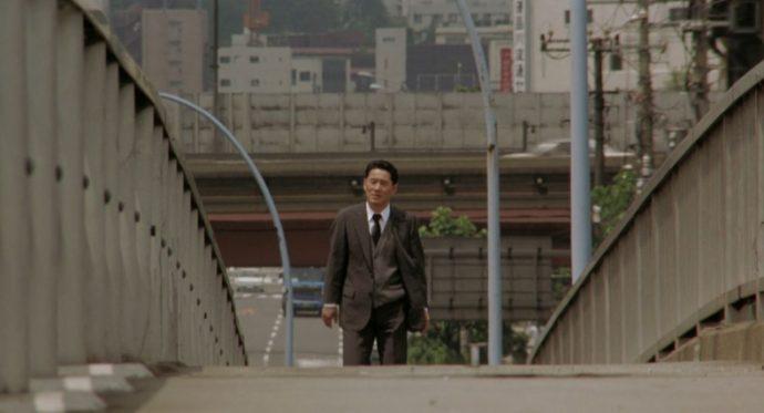 O personagem interpretado por Kitano anda por uma ponte em direção a câmera