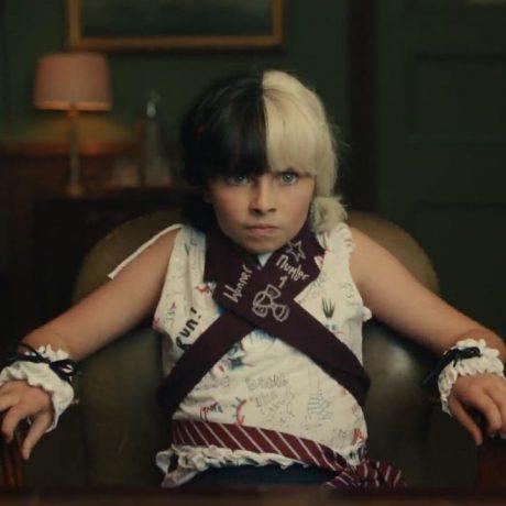 Cena do filme em que a Cruella é uma criança, ela usa uma camisa sem manga e munhequeiras brancas com laços pretos.