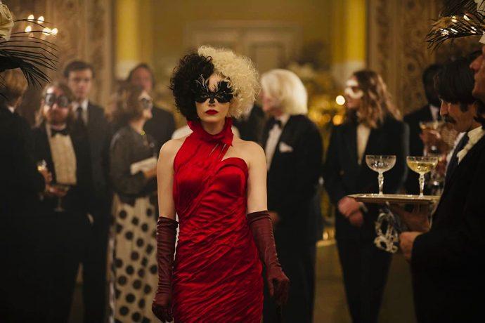 Emma Stone usa um vestido vermelho, luvas também vermelhas e uma máscara preta.
