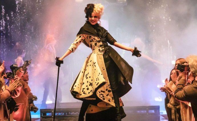 Emma Stone em meio a um desfile, ela usa um vestido com estampa de dálmata.