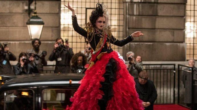 Emma Stone em Cruella, veste uma roupa vermelha e preta com detalhes em dourado.