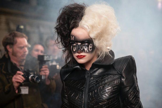 """Emma Stone em cena do filme, ela usa uma roupa preta e uma maquiagem no rosto que lembra uma máscara onde se lê """"the future"""".."""