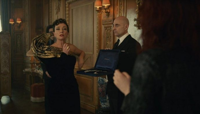 Emma Thompson como Baronesa usando um vestido elegante, enquanto fala com alguém que só aparece parcialmente no quadro.