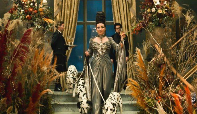 Baronesa desce uma escada usando um vestido chique, com ela há três dálmatas.